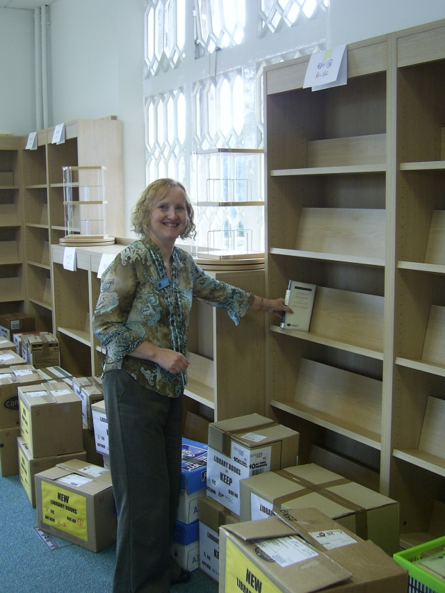 Putting the first book on the shelf - new Dixie Grammar School Library 2009